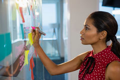 Female executive writing on glass board with a marker. In office Stock Image