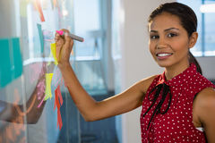 Female executive writing on glass board with a marker in office. Portrait of female executive writing on glass board with a marker in office Stock Photo
