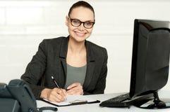 Female executive writing on notepad Royalty Free Stock Photo