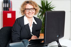 Female executive writing notes on clipboard Royalty Free Stock Photography
