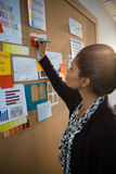Female executive writing on sticky note at bulletin board Royalty Free Stock Image