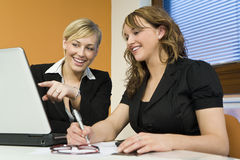 Female Executives. Two attractive young female executives working together on a laptop royalty free stock images