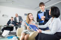 Female Executives Discussing Over Clipboards In Office. Female executives discussing over clipboards with male colleagues in background at office stock photo