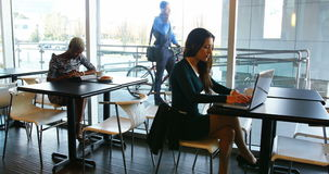Female executives using digital tablet and laptop stock video footage