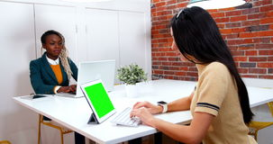 Female executives using laptop and digital tablet at desk stock video footage