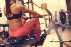 Female exercise on machine for forming muscles. In gym Stock Photos