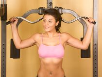 Female exercises on weight-lifting machine. Young woman works out in gym on weight-training machine, working on her shoulder muscles Stock Photos