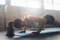 Female exercising on fitness mat at gym stock photography