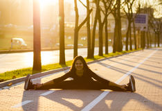 Woman exercising. Young woman doing yoga or stretching on paved lane in urban environment Stock Photography