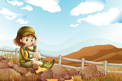 A female explorer sitting above the rock near the fence Stock Photo