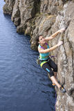 Female extreme climber conquers steep rock Royalty Free Stock Image