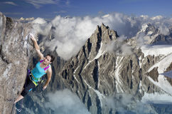 Female extreme climber hanging on cliff over the Stock Photo