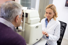 Female eye specialists determines diopter using apparatus Stock Photo
