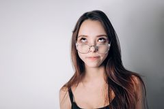 Attractive Brunette Girl Funny woman with glasses looks up. stock image