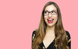 Female eye wear. Attractive brunette girl looking to the side wearing dress retro vintage style over pink background.  royalty free stock images