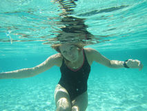 Female with eyes open underwater in ocean Stock Image