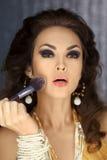 Female face with brush applying make-up Stock Image