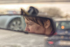 Female Face in Car's Rear View Mirror Stock Photo