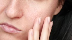 Female face close-up. Texture of problem skin with enlarged pores. The woman touches the skin of her face with her hands