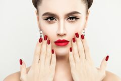 Female Face Close up. Woman Touching her Face her Hand. With Manicure. Red Makeup Lips and Red Nails Stock Photos