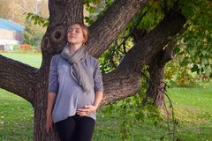 Female face, closed eyes close-up, A pregnant woman standing alone in the park, melancholy eyes closed. Female face, closed eyes close-up, A pregnant woman stock image