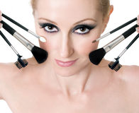 Female face with cosmetic makeup brushes royalty free stock photo
