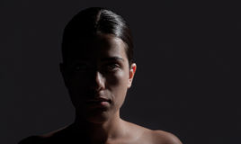 Female Face on Dark Background. Horizontal photo of a female face, half lit on dark gray background. The girl stares without an expression, without any emotion Stock Images