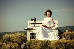 Female Face. Issues affecting girls. Girl with vintage typewriter and camera on bench. Education and knowledge. Lady in white dress and wreath on sunny day Stock Images