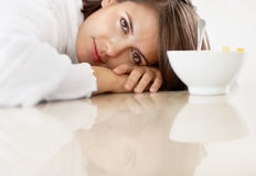 Female with face on the kitchen counter by a bowl Royalty Free Stock Photography