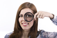 Female face looking through magnifier Stock Photos