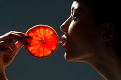 Female face with pummelo. Over dark  background Stock Images