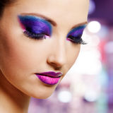 Female face with purple fashion makeup. Beautiful female face with bright purple fashion makeup stock images
