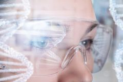 A female face in virtual reality glasses with dna image model reflection on them. A closeup of a female face wearing transparent virtual reality glasses with dna stock photos
