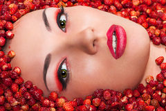 Female face in wild strawberry Royalty Free Stock Photo