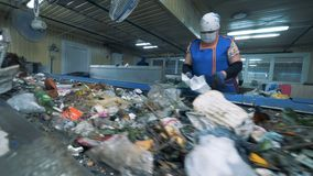 Female factory employee is sorting waste for further recycling. Waste recycling plant.