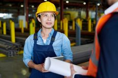 Female Factory Worker Listening to Foreman. Waist up portrait of cheerful female factory worker wearing hardhat smiling happily while talking to foreman in stock images