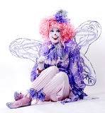 Female Fairy Clown. Sitting fairy clown with wings and wand Stock Photography