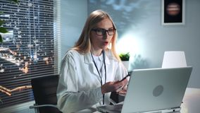 Female family counselor speaking with her patient by video call online on her personal computer. In cosy light office in the evening stock footage