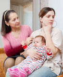 Female family problems. Mature women comforts crying adult daughter with baby at home stock photos