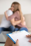 Female family psychologist filling information about couple in m stock photos