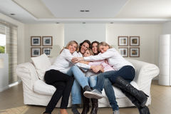 Female family sofa cuddle. A group of five happy women of different ages hugging in the living room Stock Photo