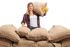 Female farmer behind a pile of burlap sacks. Looking at the camera and smiling isolated on white background Royalty Free Stock Photos