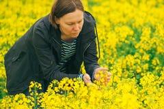 Female farmer in blooming rapeseed field Stock Photo
