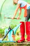 Female farmer and gardening tools in garden Royalty Free Stock Photography