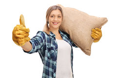 Female farmer giving thumb up and carrying a sack Royalty Free Stock Photos