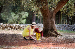 Female farmer and her little helper working in olive grove in Italy Royalty Free Stock Image