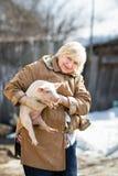 Female farmer holding  pig Stock Photo