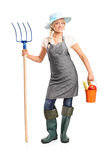 Female farmer holding a pitchfork and bucket Royalty Free Stock Photos