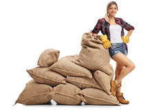 Female farmer leaning on a pile of burlap sacks stock photography