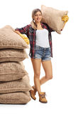 Female farmer leaning on pile of burlap sacks and holding sack o stock photography